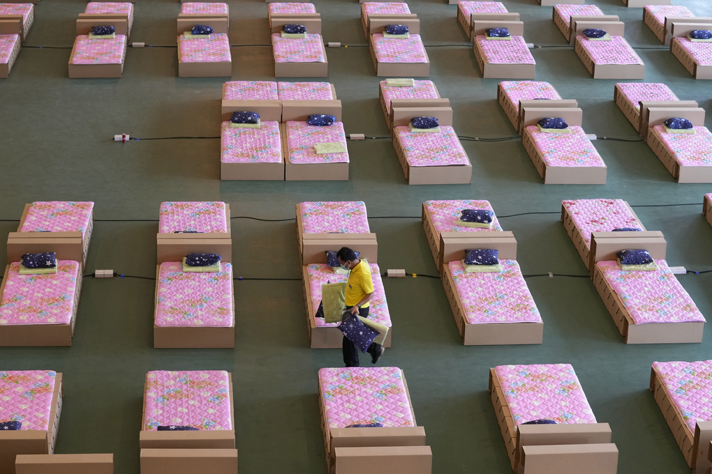 A volunteer walks past a 1,800-bed field hospital set up inside a cargo building in Don Mueang International Airport in Bangkok, Thailand, Thursday, July 29, 2021. Health authorities raced on Thursday to set up yet another large field hospital in Thailand's capital as the country recorded a new high in COVID-19 cases and deaths. The hospital, one of many already in use, was being set up at one of Bangkok's two international airports after the capital ran out of hospital beds for thousands of infected residents. (AP Photo/Sakchai Lalit)
