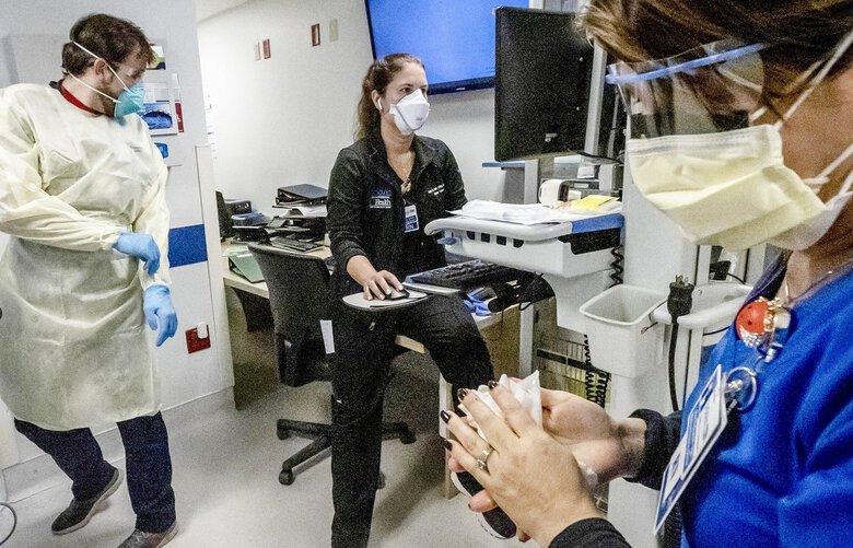 Nurse Alix Zacharski, right, sanitizes her hands as other doctors and nurses continue to care for a patient in the Medical Intensive Care Unit for COVID-19 patients at Jackson Memorial Hospital on July 23, 2021. (Jose A. Iglesias/Miami Herald/TNS) 23933205W