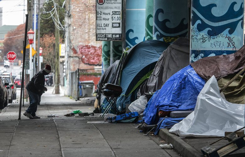 Tents line portions of the interim parking lot in Seattle under an Interstate 5 overpass in November as Kelsey Brennan from Co-LEAD and Nichole Alexander from REACH help to move tent dwellers into hotels.   (Steve Ringman / The Seattle Times)