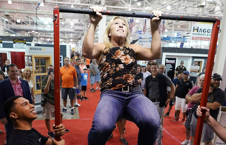 Rep. Marjorie Taylor Greene, R-Ga., does a pull-up at a U.S. Marine recruiting booth during a visit to the Iowa State Fair, Thursday, Aug. 19, 2021, in Des Moines, Iowa. (AP Photo/Charlie Neibergall) PNA707 PNA707