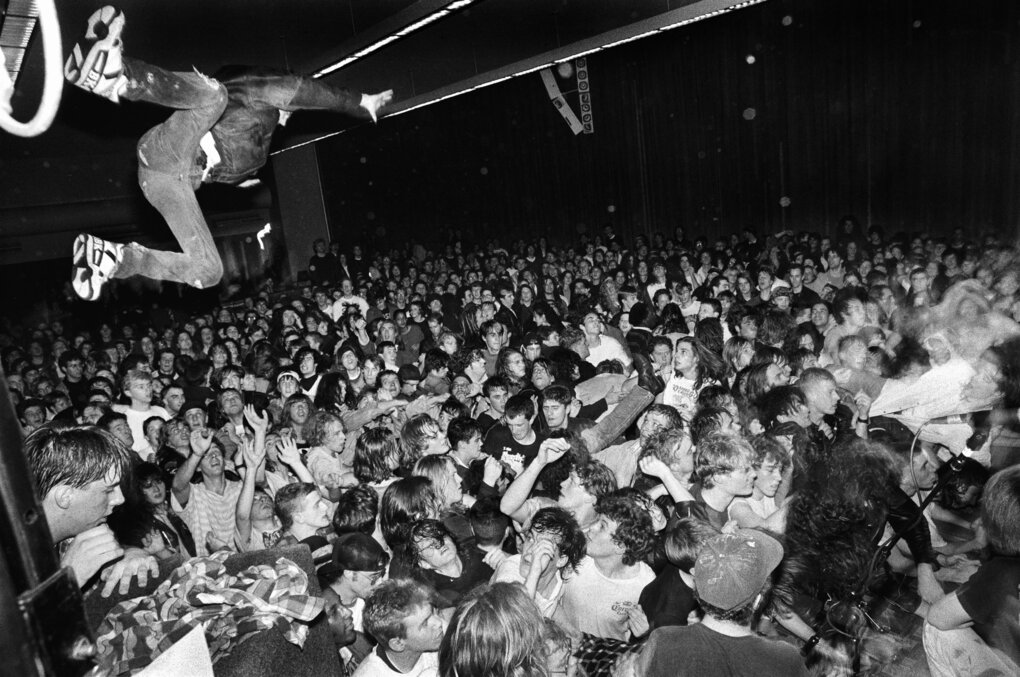 """At a 1990 Nirvana show, photographer Charles Peterson was watching a young guy get on top of a PA stack, ready to jump off into the audience. Peterson remembers tugging at the guy's pants leg, shouting, """" 'Don't do it!' I thought he was going to break his neck. But he was going to do it."""" So Peterson quickly got ready for the shot. The kid was caught by the frenzied crowd and was fine. (Charles Peterson)"""
