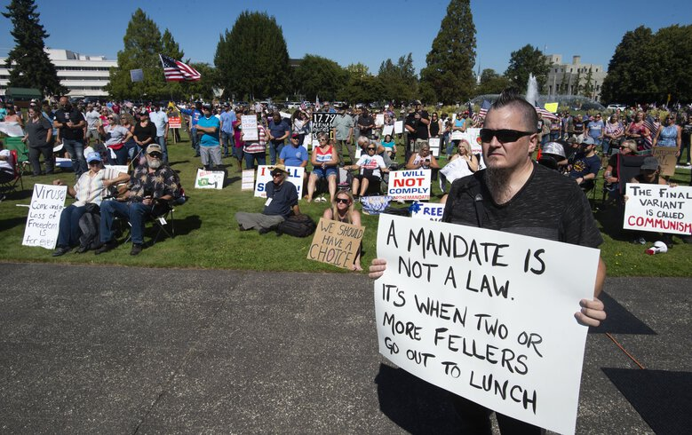 Olympia resident and state employee William Baker and others gather outside the Capitol in Olympia on Aug. 28 to protest Gov. Jay Inslee's vaccine mandate for state workers. (Drew Perine / The News Tribune via The Associated Press)