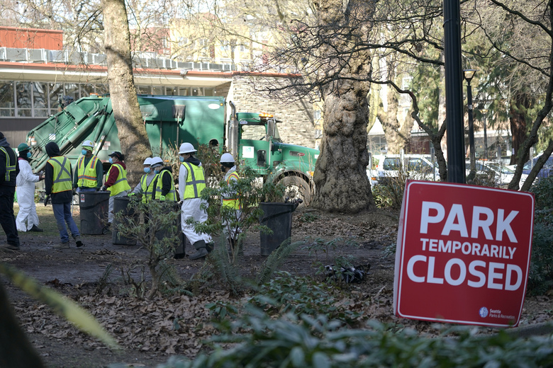 Cleanup workers gather at Denny Park near the Space Needle in Seattle on March 3, 2021. The park was cleared of several dozen tents and people lacking housing. (Ted S. Warren / AP, File)