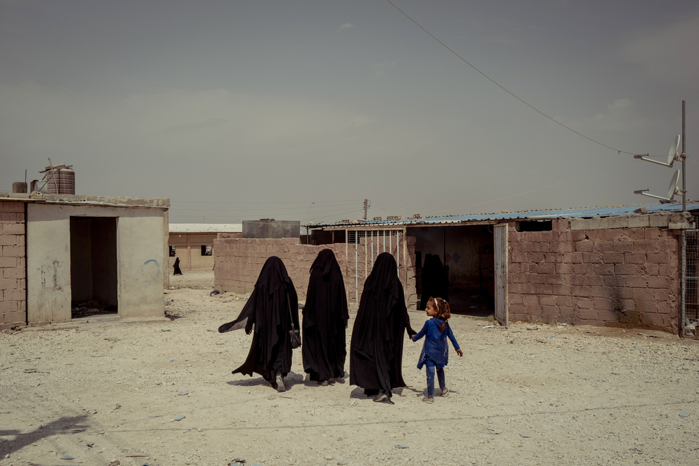 Three women and a child walk near the market in al-Hol camp. (Photo for The Washington Post by Nicole Tung)