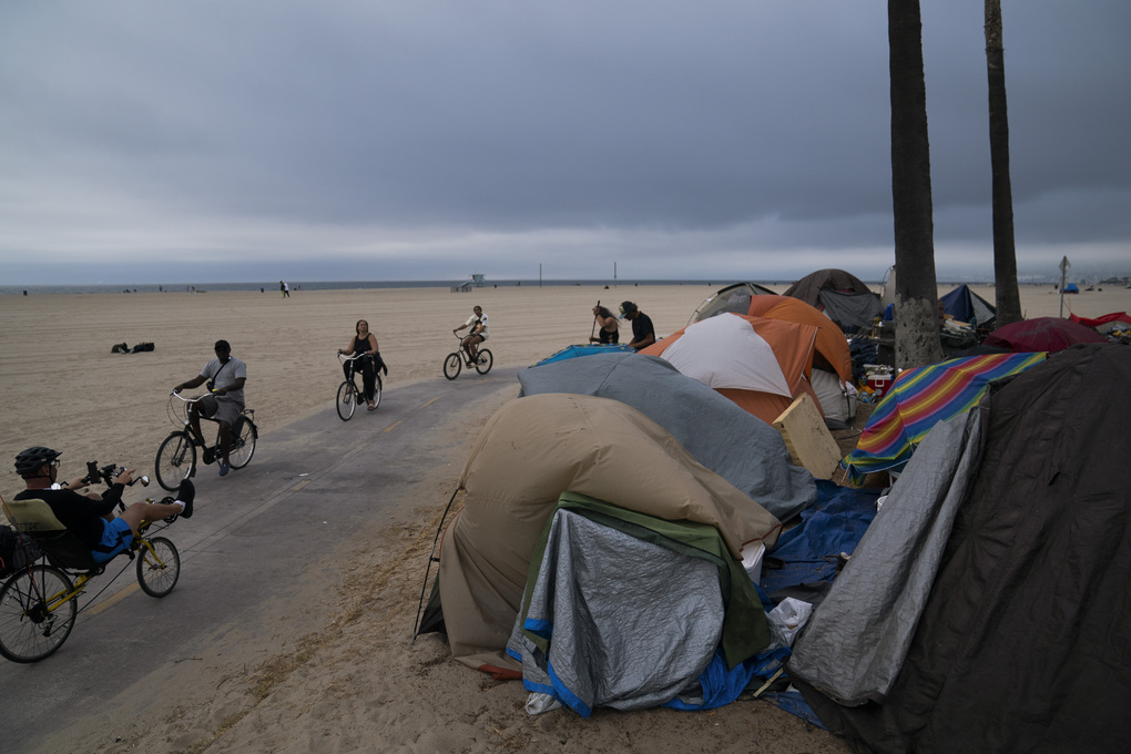 FILE – In this June 29, 2021, file photo people ride their bikes past a homeless encampment set up along the boardwalk in the Venice neighborhood of Los Angeles. The share of Americans living in poverty rose slightly as the COVID pandemic shook the economy last year, but massive relief payments pumped out by Congress eased hardship for many, the Census Bureau reported Tuesday, Sept. 14. The official poverty measure showed an increase of 1 percentage point in 2020, indicating that 11.4% of Americans were living in poverty. It was the first increase in poverty after five consecutive annual declines. (AP Photo/Jae C. Hong, File)