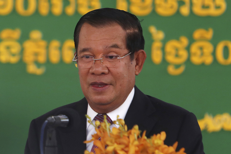 FILE – In this Feb. 7, 2021, file photo, Cambodian Prime Minister Hun Sen delivers a speech during a handover ceremony at Phnom Penh International Airport, in Phnom Penh, Cambodia. Hun Sen boasted Friday, Sept. 17, 2021, of barging uninvited into a video conference call hosted by his political opponents.(AP Photo/Heng Sinith, File)