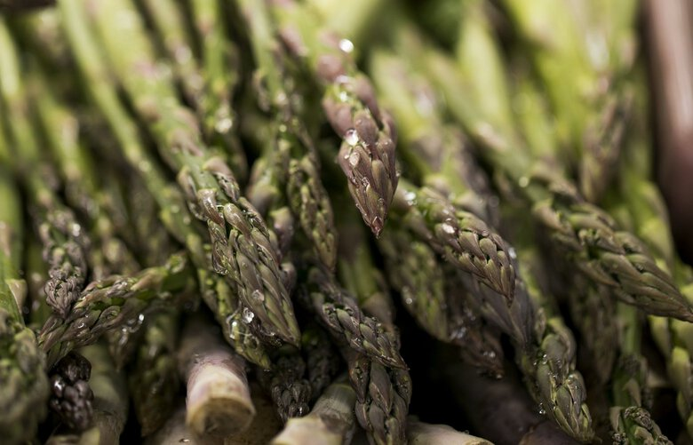 Asparagus glistens at the Alvarez Organic Farms stand at the West Seattle Farmers Market Sunday June 3, 2018. 206467